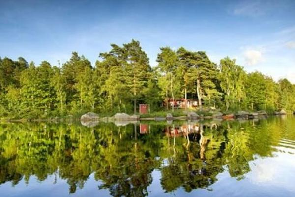 Trees and cottages are reflected in the lake